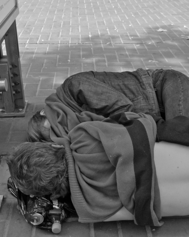 Homeless Couple Using Garbage Bag as Pillow in Front of Orpheum Theater