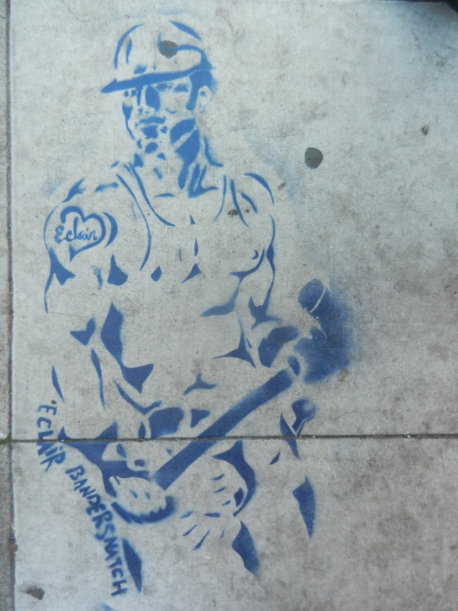A new sidewalk mural from Eclair Bandersnatch, one of my favorite muralists. Normally depicting individual women and/or lesbian couples, this construction worker represents a major departure.