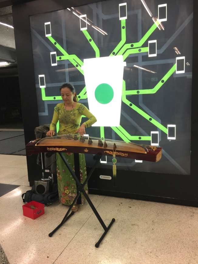 Musician Performing East Asian Music in Front of a Starbucks Ad, Powell Street Station, San Francisco, CA, 7 October 2015, 9:10 p.m.